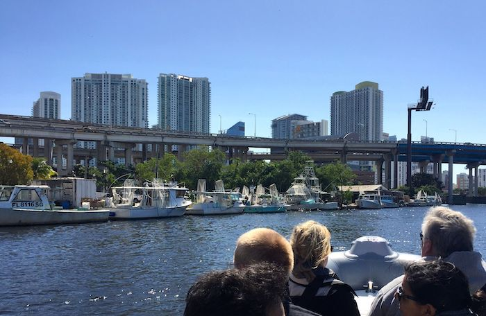 Lobster boats along the historic Miami River against the backdrop of downtown Miami on a boat tour.